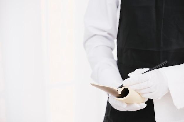 Cameriere elegante scrivere una nota Foto Gratuite