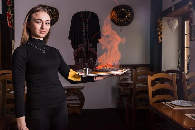 Cameriere femminile che porta carne bruciata nel ristorante Foto Gratuite