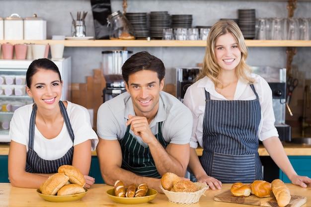 Cameriere sorridente e due cameriere appoggiato al bancone Foto Premium