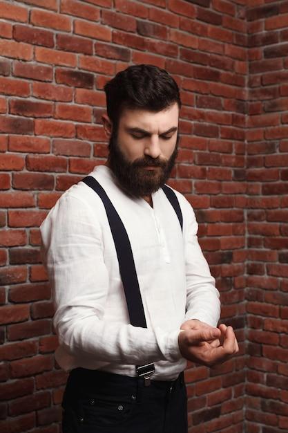 Camicia di correzione del giovane uomo bello sul muro di mattoni. Foto Gratuite