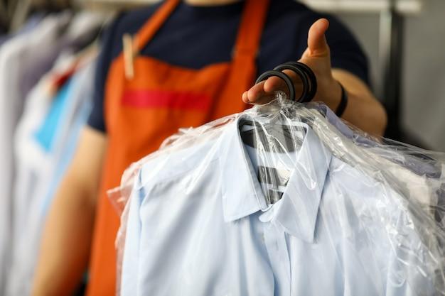 Camicia di ritorno del lavoratore di servizio di lavaggio a secco dei vestiti al cliente Foto Premium