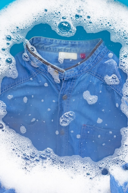 Camicia jean imbevuta di polvere detergente dissoluzione dell'acqua. concetto di lavanderia Foto Premium