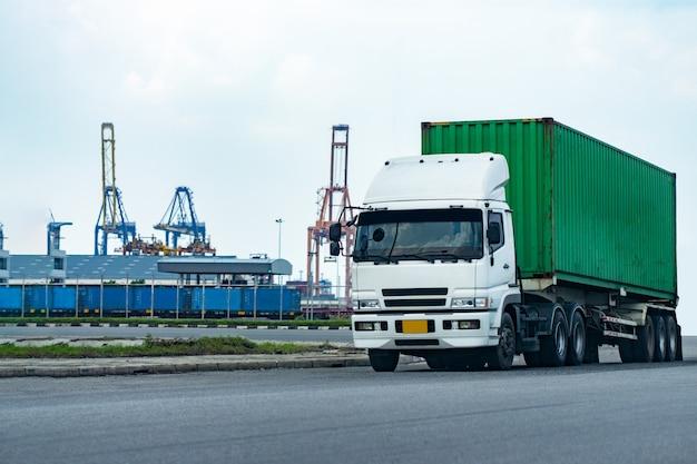 Camion portacontainer verde del carico nella logistica del porto della nave. industria dei trasporti nel concetto di affari del porto. Foto Premium