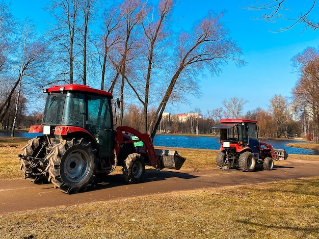 Camion rossi dei trattori nel parco della città di primavera. pulizia. inizio primavera. lavori. giornata di sole primaverile. Foto Premium