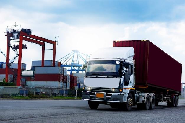 Camion rosso del contenitore di carico nella logistica del porto marittimo Foto Premium