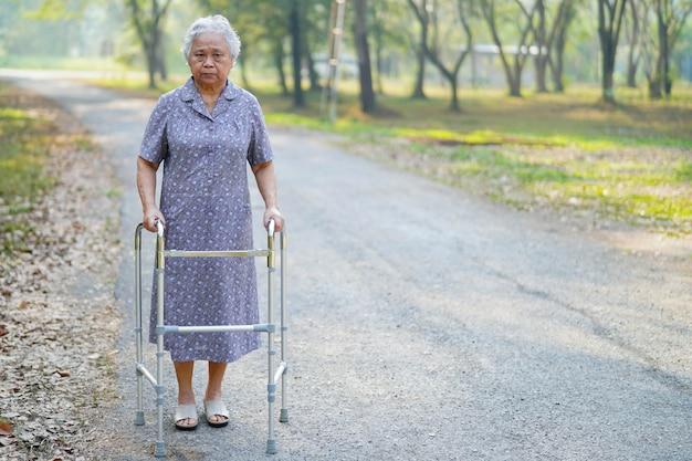 Camminata paziente della donna senior asiatica con il camminatore in parco. Foto Premium