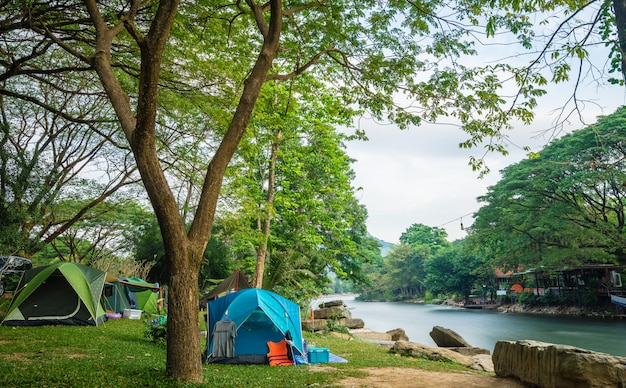 Campeggio e tenda vicino al fiume Foto Premium