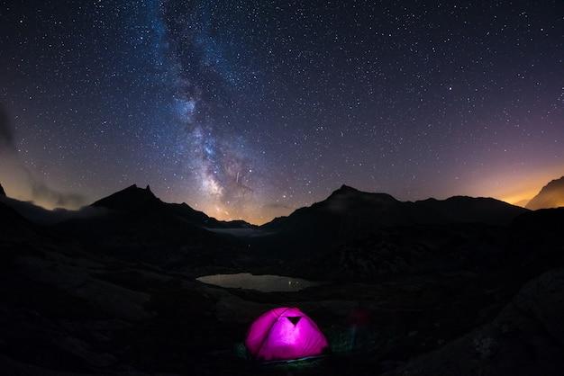 Campeggio sotto il cielo stellato e la via lattea in alta quota sulle alpi. Foto Premium