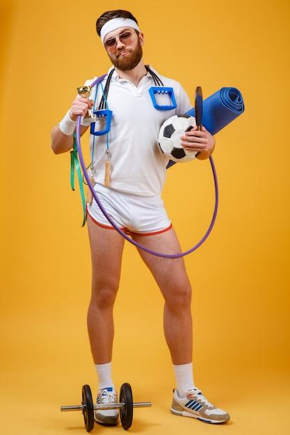 Campione soddisfatto felice dell'uomo che tiene tazza e attrezzature sportive dorate Foto Gratuite