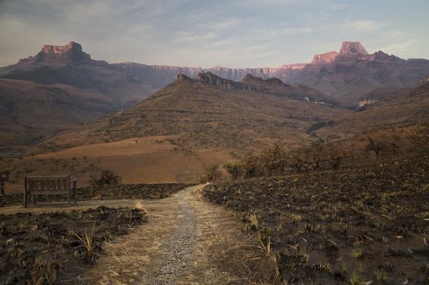 Campo di erba secca bruciata nel deserto con uno stretto sentiero e bellissime montagne rocciose Foto Gratuite