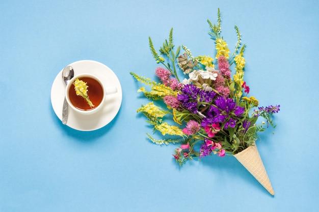 Campo fiori colorati in cono gelato cialda e tazza di tè Foto Premium