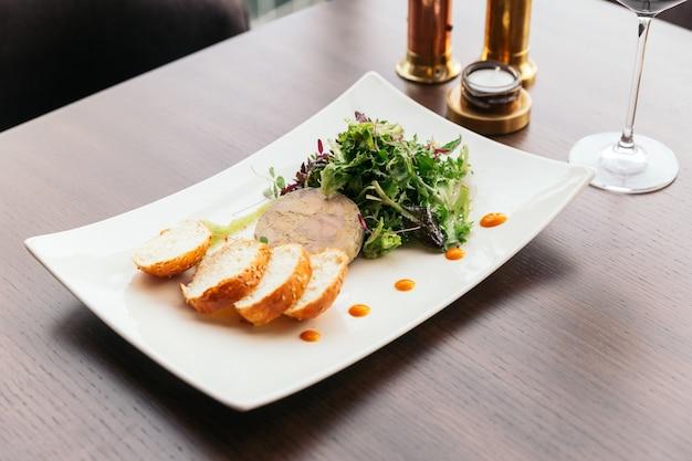 Canape con paté di foie gras e insalata servita con vino bianco. Foto Premium