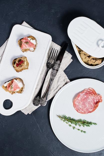 Canape con prosciutto, salame e paté d'anatra su un tagliere bianco & Foto Premium
