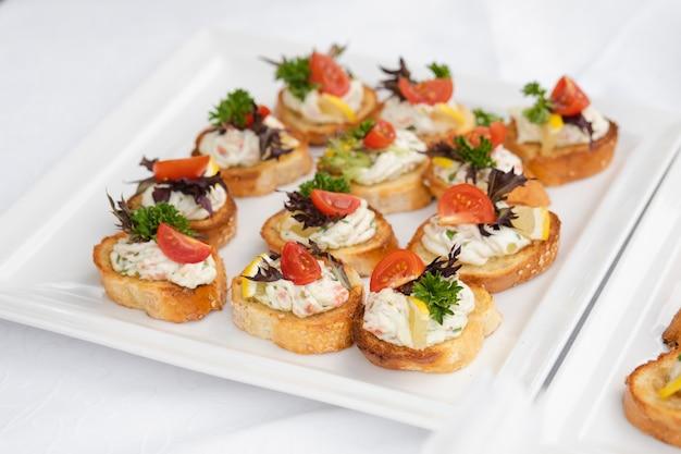 Canape deliziose con la salsiccia e il pomodoro. tartine sui piatti ceramici bianchi al ricevimento nuziale. Foto Premium
