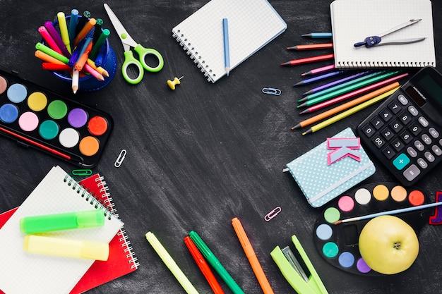 Cancelleria creativa colorata, calcolatrice e apple su sfondo scuro Foto Gratuite