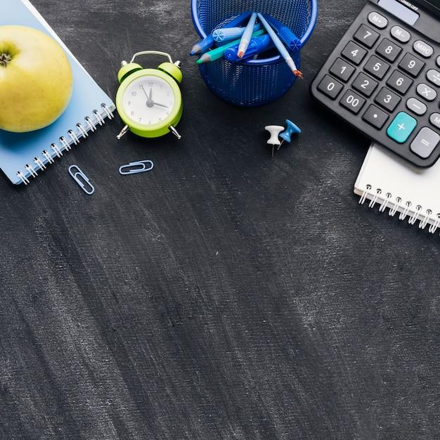 Cancelleria per ufficio, calcolatrice e apple su sfondo grigio Foto Gratuite