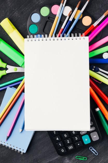 Cancelleria vibrante e calcolatrice sotto notebook bianco Foto Gratuite