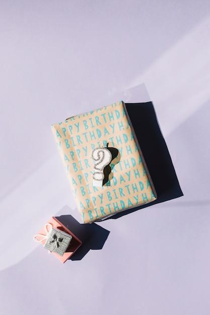 Candela del punto interrogativo sui contenitori di regalo avvolti isolati sopra fondo bianco Foto Gratuite