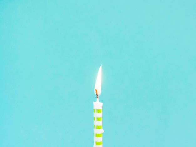 Candela di compleanno del primo piano su fondo blu Foto Gratuite