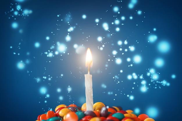 Candela di compleanno sul delizioso bigné con caramelle su sfondo azzurro. holiday biglietto di auguri Foto Premium