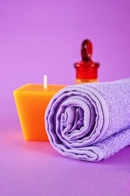 Candela gialla e olio aromatico, asciugamano viola Foto Premium