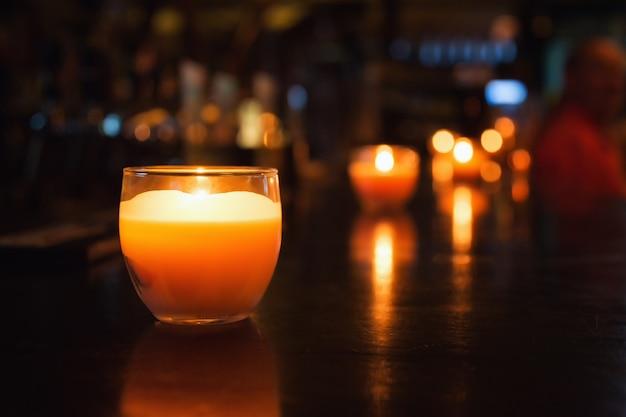 Candela in un bicchiere. foto della reception del bar o del ristorante. messa a fuoco selettiva con bokeh Foto Premium