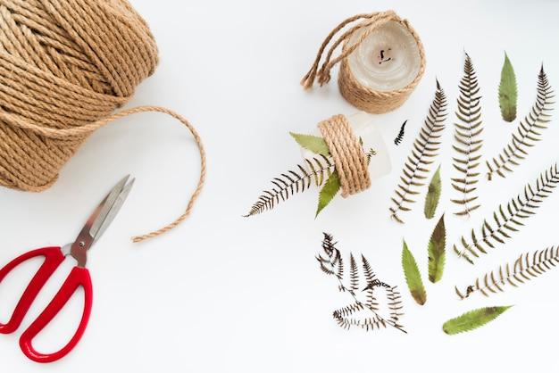 Candela legata con corda e foglie su sfondo bianco Foto Gratuite