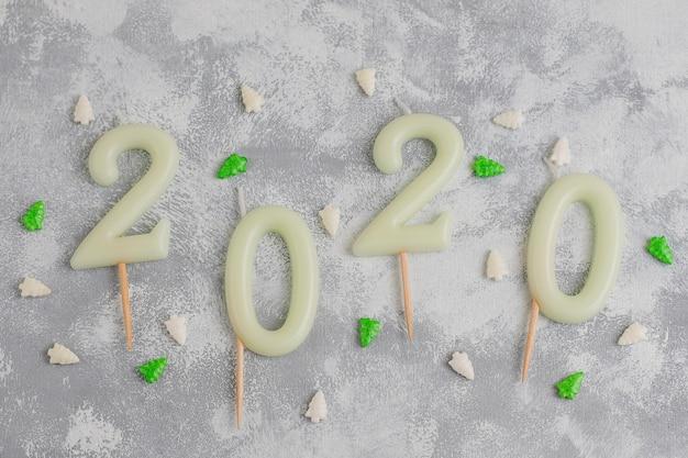 Candele a forma di numeri 2020 come simbolo del nuovo anno accanto a caramelle scintillanti a forma di natale su un tavolo grigio. vista dall'alto, piatto Foto Gratuite
