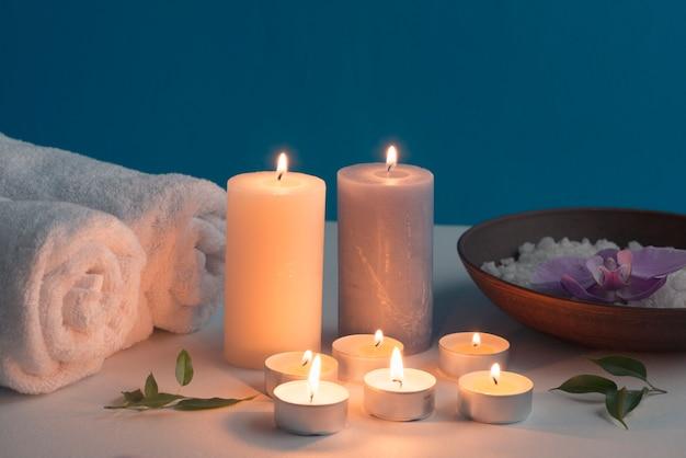 Candele accese, asciugamano arrotolato e sale da bagno termale sul tavolo Foto Gratuite