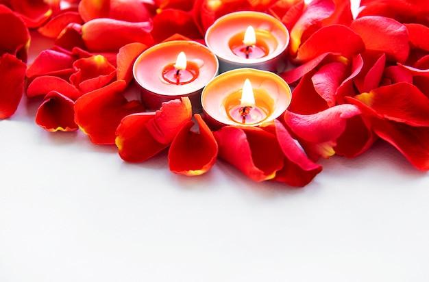 Candele accese in petali di rosa Foto Premium
