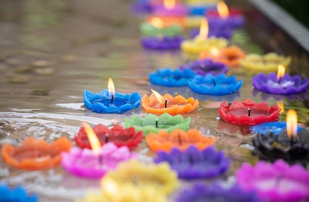 Candele colorate a forma di fiore galleggiano nell'acqua. Foto Premium