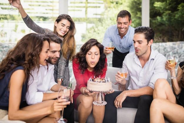 Candele di compleanno di salto della donna con il gruppo di amici Foto Premium