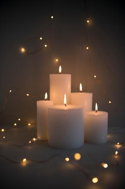 Candele illuminate circondate da luci fata incandescente su sfondo scuro Foto Gratuite