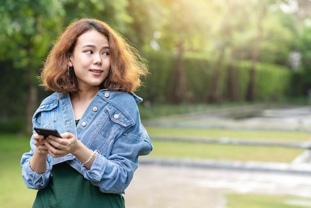 Candido di giovane asiatico attraente felice con il progettista o l'influencer femminile alla moda dei capelli castana ricci d'avanguardia che sta nel giardino a casa fuori facendo uso dello smartphone che guarda al lato per la pubblicità. Foto Premium