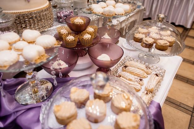 Candy bar con dolci mousse, bignè e pasticceria sul tavolo viola Foto Gratuite