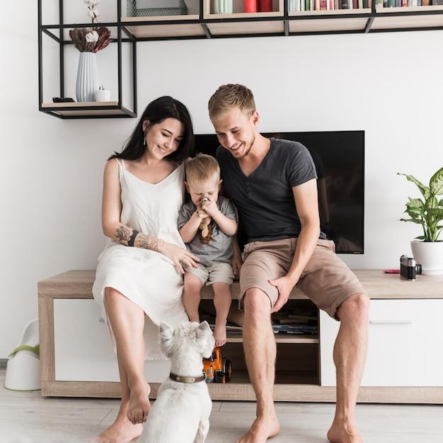 Cane bianco che esamina le giovani coppie sorridenti che si siedono con il loro figlio davanti alla televisione Foto Gratuite