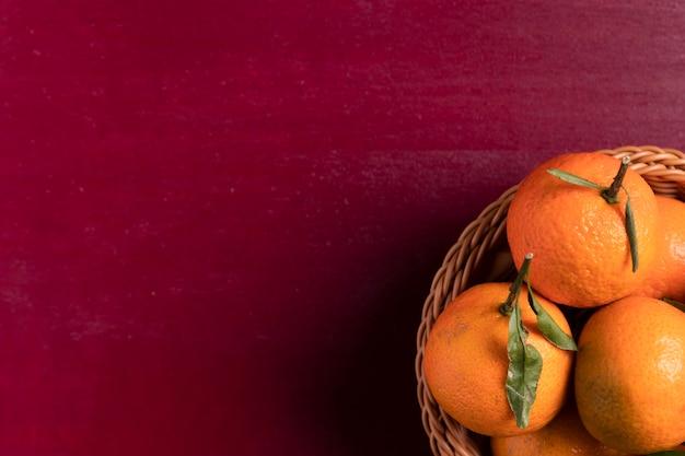 Canestro dei mandarini su fondo rosso per il nuovo anno cinese Foto Gratuite