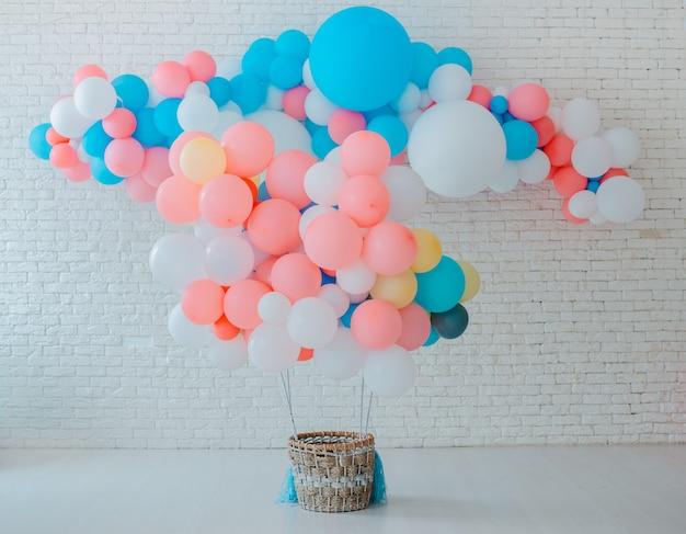 Canestro dei palloni per il volo aereo sul mattone bianco con fondo rosa blu luminoso con spazio libero Foto Premium