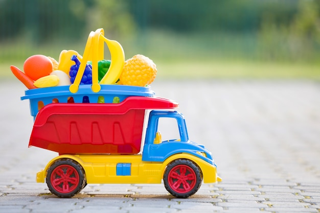 Canestro di trasporto del camion dell'automobile del giocattolo con la frutta e le verdure del giocattolo. Foto Premium