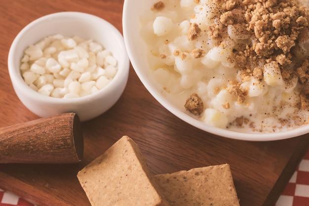 Canjica dolce del dessert brasiliano di cereale bianco con il dolce di pacoca Foto Premium