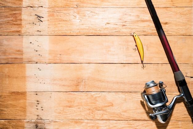 Canna da pesca con esche da pesca gialla sulla tavola di legno Foto Gratuite