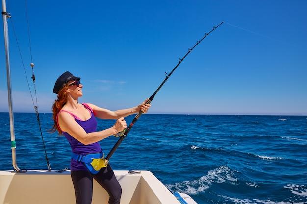 Canna da pesca della ragazza della bella donna che trolling in barca Foto Premium