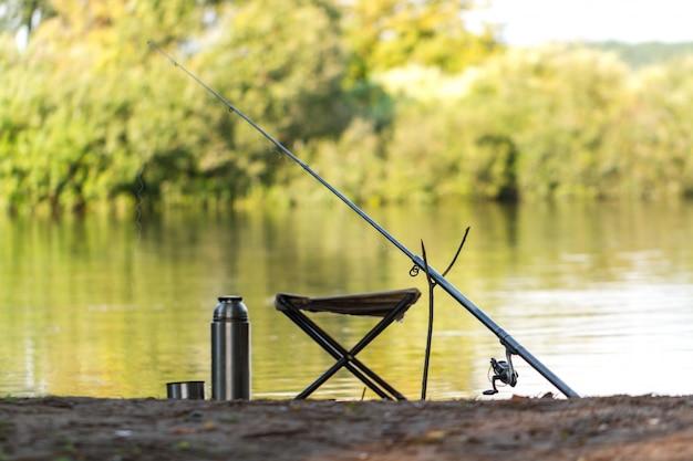 Canna da pesca, thermos, sedia da pesca sullo sfondo del lago. pesca. Foto Premium