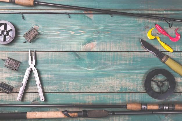 Canne da pesca, attrezzi da pesca, linee, coltello e alimentatori su legno verde Foto Premium