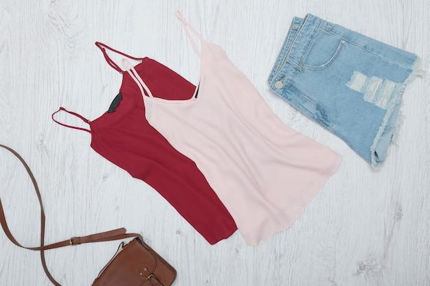Canotta rosa e bordeaux, pantaloncini di jeans strappati. concetto alla moda Foto Premium