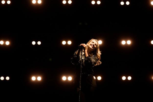 Cantante che canta al microfono. cantante in silhouette Foto Premium
