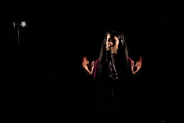 Cantante donna cantando una canzone nello studio di registrazione. Foto Premium