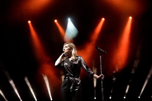 Cantante in scena nel club. illuminazione scenica brillante. Foto Premium