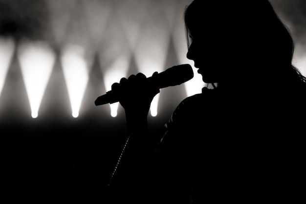 Cantante in silhouette. chiuda sull'immagine del cantante dal vivo sul palco Foto Premium
