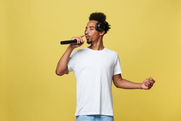 Cantante maschio afroamericano bello che esegue con il microfono. Foto Premium